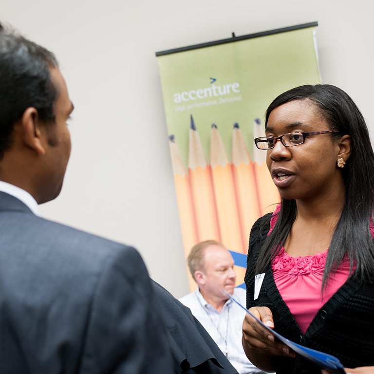A student talking with a recruiter at a career fair.
