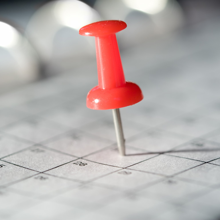 Thumbtack sticking into a calendar