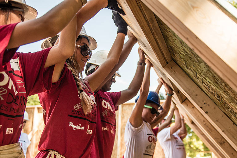 Students work together to raise a framed wall on a Habitat for Humanity build