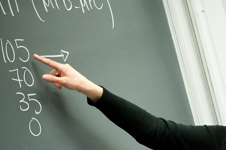 A female faculty member pointing at chalkboard while teaching